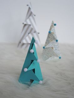 A sheet of fancy card stock, a few clever cuts, and a couple of folds is all you need to make standing, Christmas trees.