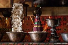 Tibetan buddhist offerings, bronze bowls, silver goblet, white feathers and maroon / green paper mandala on the table inside monastery preying hall in Ladakh, India. art / boho / asian / photo / wall decor / tibet  https://www.etsy.com/listing/216815969/tibetan-buddhist-offerings-bronze-bowls