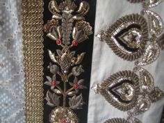 Zardozi is heavy and ornate embroidery of Persian origin in   which gold, silver and metal wires are couched onto fabric with a needle and thread. It is used to create badges for the military and ceremonial robes.