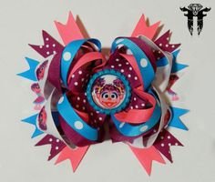 This super cute Abby Cadabby inspired hair bow measures approximately 5.5 x 5 inches!!  Stacked and stacked, it features many different colorful ribbons to surely match any Abby themed outfit! I have sealed Abby in a bright blue flattened bottle cap to the center of the bow. Her portrait is protected by an epoxy dome that slightly magnifies the design- bringing it to life! This bow is available with either an alligator clip or a french barrette.