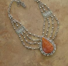 Stunning necklace with a large semi precious orange jasper stone, softly   accented by cascading chains.