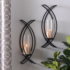 "Want to give your living space a twist? Try our ""Charlie Crisscross Sconces!"" After All, the best things in life come in pairs. This set accommodates two pillar candles and is sure to add depth and architectural flair to your wall decor."