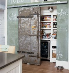 """This unique pantry portal was a vintage door from an old New Orleans bank safe and is installed on a sliding track.""  absolutely love this pantry, the idea is so cool of refurbishing a vintage piece and the chalkboard wall is great!"
