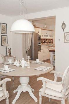 okragła biała lampa nad stołem,nowoczesna lampa nad okrągłym stołem,lampa do jadalni,aranżacja otwartej jadalni z kuchnią,kuchnia z jadalnią,prowansalska jadalnia z otwartą kuchnią,francuskie krzesła z bielonego drewna,okrągły stół na białej nodze,stylowy drewniany stół,biały stół z drewnianym blatem,drewniana ławka ze skrzynkami,zasłony jako scianki działowe w mieszkaniu,rolety rzymskie,aranżacja jadalni w prowansalskim stylu,francuska jadalnia,projekt otwartej kuchni z jadalnia w stylu…