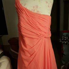 Coral bridesmaid dress David's bridal coral bridesmaid dress only wore once for the wedding... there is a small stain on the back of the dress at the bottom by the hem, not noticeable unless looking for it! One shoulder chiffon dress, bottom one side is a bit longer than he other side and ruched top... clip did come off but zips up great and stays closed !    Best offer! David's Bridal Dresses