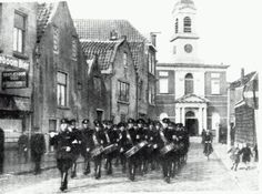 De WA van Overschie marcheert de Zestienhovensekade op  op de achtergrond de Delftweg met de RK Kerk Sint Petrus' Banden