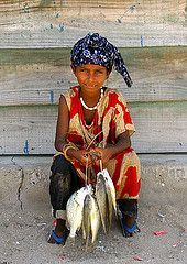 Afar Girl Holding Fishes,  Thio Eritrea (Eric Lafforgue Photography) Tags: africa portrait food fish color colour girl vertical outdoors photography day african redsea fulllength fishes woodhouse oneperson traditionalculture eritrea hornofafrica brownhair eastafrica eritrean traditionalclothing realpeople lookingatcamera danakil dankali thio africanethnicity italiancolony indigenousculture 89years onegirlonly serenepeople danakildepression afardepression italiancolonialempire