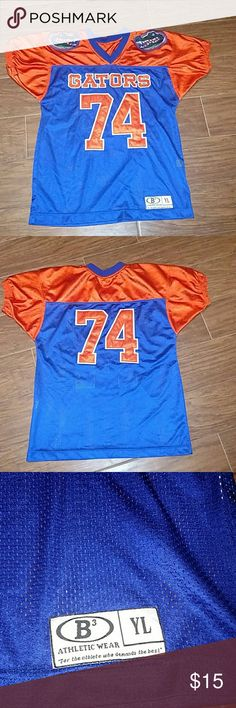 University of Florida Gators Jersey University of Florida Gators Jersey. V-Neck Jersey with raised stitched lettering and numbers. 2 Gator patches on both shoulders. Youth L. Measuring 20 inches arm pit to arm pit. Should easily fit S/M adult as well. Shirts & Tops