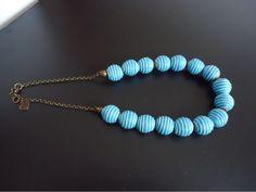 Colar de bolinhas azuis revestidas de fios de algodao. R$25,00