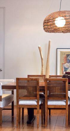 En el comedor la madera es protagonista. Una original mesa maciza construida con un patch de tablones de diferentes maderas (Fernando Moy) se acompañó con sillas con respaldo de esterilla (Bacano) y, en la cabecera, dos sillones con fundas de loneta blanca (Laura O.). Una omnipresente lámpara colgante de cintas de mimbre (Walmer) ilumina el espacio, mientras detrás, sobre un mueble vajillero, descansan esculturas del Norte argentino, una lámina de Pablo Picasso enmarcada y dos elegantes…