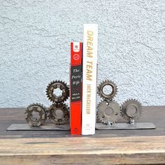"""Once an adventurous life on the road this Motorcycle Gear Bookend has a story to share. Hand-crafted and created from repurposed motorcycle parts this will surely be all the talk in any moto enthusiast office or den. DUAL-G E A R - B O O K E N D S - D E S C R I P T I O N ------------------------------------- These parts once powered man and machine, but years of neglect left this iconic motorcycle destined for the scrapyard until it was rescued by """"Old Ducs."""""""