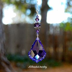 This hanging purple teardrop prism crystal suncatcher can be hung on the rearview mirror, in a window, attached to an existing chain from the ceiling light/fan chain or wherever you choose! This purple crystal suncatcher is uniquely designed with a beautiful purple violet baroque prism crystal that measures approximately 1.5 long and 1 wide (at the largest part). The purple prism is quality wire wrapped for strength with flawless tanzanite Swarovski crystals, fancy silver bead caps and…