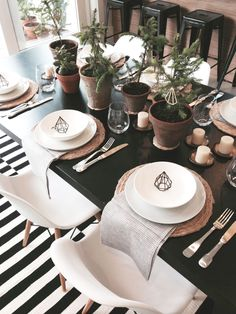 Clean and simple Christmas tablescape with candles, greenery and black and white geometric accents.