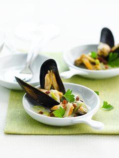 Bereiden: Was de mosselen. Stoof de fijngesneden ui en selder in wat boter. Voeg de mosselen toe, kruid met peper van de molen en zout. Snijd ondertussen de sjalotjes heel fijn en de prei in fijne reepjes. Stoof in de resterende boter. Giet de mosselen in een platte schaal. Haal ze uit de schelp, maar bewaar 10 mooie dubbele schelpen. Tapas, Fish Recipes, Seafood Recipes, Healthy Recipes, Gourmet Appetizers, Bistro Food, Good Food, Yummy Food, Fish Dishes