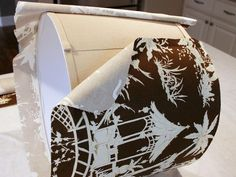 Brown Patterned Fabric Being Wrapped Onto Lampshade