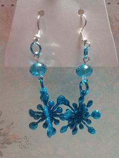 These adorable earrings are handmade by me. They each feature a bright blue sparkly snowflake and a matching blue bead attached with bright blue jump rings. $4
