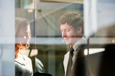 behind a glass window a businessman and businesswoman discussing work