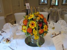 Horse racing party table centre in bright yellows, oranges and lime greens, with a glittery gold and small silver horseshoe. Flowers include Gerberas, Roses, Calla Lilies and Amaranthus. Horse Racing Party, Amaranthus, Table Centers, Calla Lilies, Surrey, Corporate Events, Centre, Lime, Roses