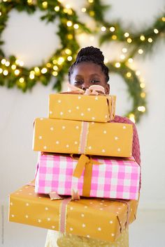 A cute young African girl holds a big pile of Christmas presents with some decorations in the background Stylist: Bielle Bellingham Photographer: Micky Wiswedal African Girl, Young Black, Christmas Presents, Hold On, Stylists, Gift Wrapping, Decorations, Big, Cute