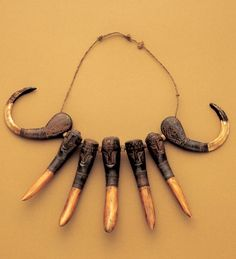 "Man's necklace from Central Indonesia(Sulawesi)      Central Indonesia(Sulawesi)  Crocodile teeth, wild boar fangs, wood      Length 56cm      The tora tora is a headhunter's necklace and formed part of a warrior costume. A man bearing the title, ""mother of tradition,"" wears this necklace, which is exclusive to persons of such elevated rank."