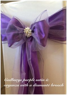 White chair cover with double cadburys purple sashes and brooch. Available to hire in Swansea, Cardiff, Neath, Bridgend, Llanelli, Carmarthen and surrounding areas of South Wales from www.affinityeventdecorators.com