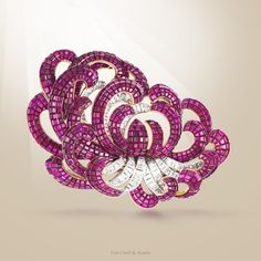 """Van Cleef & Arpels """"Art of Clip"""" exhibition in Moscow. The 1930s – a period of intense ingenuity for the Maison. The patent for the Mystery Set™ was registered in 1933: a revolutionary technique which consists in hiding the metal to give pride of place to the colored stones - Chrysanthemum clip, 1937, platinum, yellow gold, rubies, diamonds. Find more about this fascinating technique."""