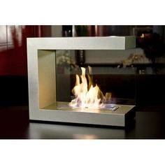 """New Orleans-based Brasa Fire's """"Camden"""" has a unique asymmetrical shape. A glass backing means you can place the portable unit against a wall. It comes with a Slim Burner with Brasa home fragrance system, long lighter and control wand tool. 23.75 inches high by 20 inches wide by 10.5 inches deep. In silver or slate. $585. Amazon.com, Allmodern.com and other online vendors."""
