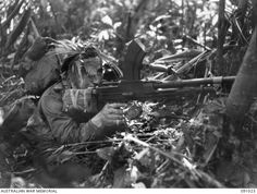 Private John Davies, Australian Infantry Battalion, conceals himself behind a tree with a Bren light machine-gun during an attack against the Japanese at the Hatai Junction on Buin Road,. Light Machine Gun, War Film, Film Inspiration, Troops, Soldiers, D Day, British History, Military History, World War Two