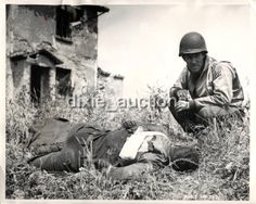 1944- U.S. 5th Army soldier comforts a badly wounded comrade while awaiting ambulance in Cisterna, Italy.