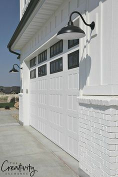 Transform and update the exterior of your home instantly by replacing garage doors with a more modern garage door design. We're showing you garage door styles to consider and what you need to think about when choosing modern garage door designs. Outdoor Garage Lights, Garage Door Lights, White Garage Doors, Modern Garage Doors, Garage Door Design, Garage Lighting, Exterior Garage Lights, Exterior Lighting Fixtures, Outdoor Farmhouse Lighting