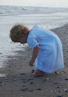 Sweet little girl searching for seashells