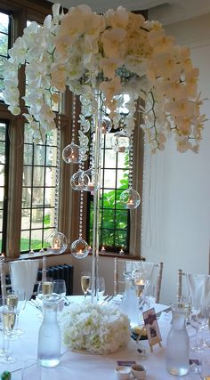 Stunning silk orchid table centres with hanging glass globes containing tea lights from Essential Wedding Hire