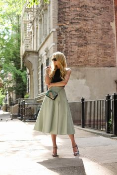 Blair Eadie is wearing a black top from Tibi, pale green full skirt from Alice + Olivia and shoes, bag and sunglasses from Emporio Armani