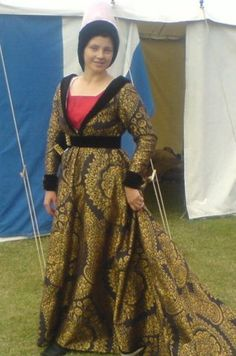A burgundian gown in gold and black silk/linen brocade, lined with gold silk taffeta, the collar, cuffs and hem in silk velvet. Black silk velvet belt with goldplated buckle. A hennin in silk taffeta sporting a silk velvet lappets/hood and a silk veil. the gown is worn on a woolen kirtle with a silk plackard. All garments are handstitched-OMG how gorgeous.  If only I could sew!!