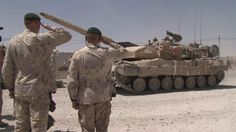 Canadian soldiers saluting as tanks roll past in Afghanistan.