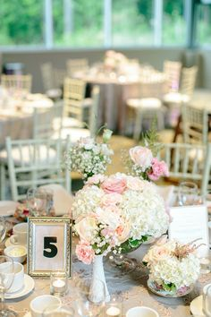 Vintage wedding centerpieces: footed comports and milk glass vases with an eclectic mix of soft blooms, DIY table numbers in gold frames, cream chivari chairs.