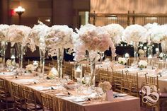 Ethereal White Wedding Tablescape in Manhattan. High centerpieces and low arrangements, composed of white phalaenopsis orchids and hydrangea, cream vendela roses and creme de la creme roses, accented with hanging crystals and glass-stemmed floating candles. Photo by Jasmine Hsu. #tablescapes