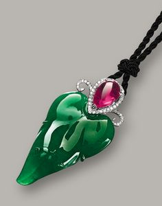 JADEITE, PINK TOURMALINE AND DIAMOND PENDANT The translucent jadeite of emerald green colour, carved as a leaf, surmounted by an inverted pear-shaped pink tourmaline weighing approximately 2.40 carats, decorated by brilliant-cut diamonds, strung on a black cord, length approximately 620mm, mounted in 18 karat white gold.