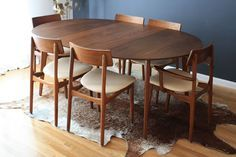 """smaller, round not oval; Mid-Century Modern Round Dining Table with Leaves This vintage Mid-Century walnut dining table comes with two leaves to extend it another 21"""" for extra guests. It is in great condition with minor wear. We are selling it as a set with six chairs (more details in Seating). Measurements: 47.5""""diameter x 29.5""""H"""