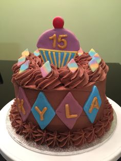 A Jaffa cake with ganache finished and fondant details. Cupcake shaped fondant topper.