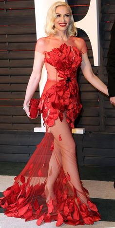 GWEN STEFANI makes her official red carpet couple debut at the Vanity Fair Oscar Party with Blake Shelton in a majorly revealing Yanina Couture floral gown, Jimmy Choo clutch, red Christian Louboutin heels and Norman Silverman diamonds (he was wearing jeans, of course).