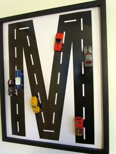 Race car monogram wall art for kid's room. Would be easy to draw & paint in the road letter. Use a canvas or framed poster board. Or paint directly on a sheet of metal and add magnets to the bottom of cars so they can be moved all over the road. Frame and attach to studs in wall (low enough to be within child's reach) for sturdy, interactive wall art!