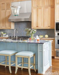 """It was a slab of rare Blue Macaubas quartzite — now on the island — that caught their eye. """"The watery blues felt warm and cool at the same time,"""" says designer Katie Collins. She and her partner, Martha Sweezey, picked up the blues with a Moroccan tile backsplash and gave the white oak cabinetry a cerused finish to bring out the grain. """"It's natural and handcrafted — a new direction after the white, industrial look."""""""