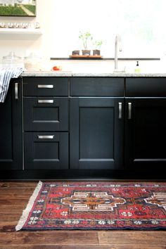 Black kitchen cabinets, marble benchtop, rug...
