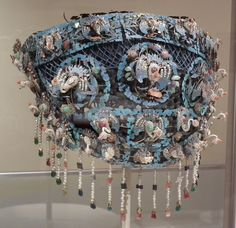 Chinese artist | Bridal headdress, 1800s | Kingfisher feather, silk, enamel, brass, pearls, coral, assorted semi-precious stones. This headdress features metal mounts into which iridescent blue feathers of the Kingfisher have been laid. The crown is further ornamented with figures including numerous small cranes of pearls and semiprecious stones. The long strands of pearls would hang down around the bride's face and be drawn aside to give the bridegroom a glimpse of his betrothed.
