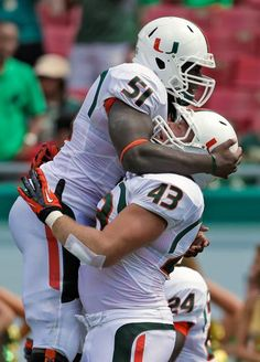 Miami's Shayon Green is embraced by Sean Harvey after falling on a fumble by South Florida quarterback Steven Bench in the end zone for a touchdown Saturday in Tampa. (Chris O'Meara/AP)