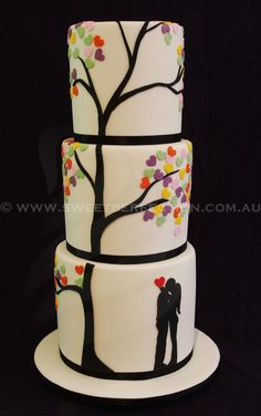 Six-tiered white wedding cake with Love Heart Tree motif and custom silhouette. By Sweet Perfection.