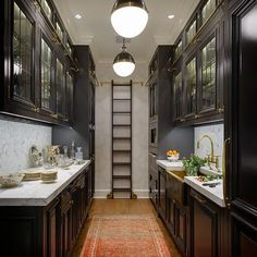 Black Galley Style Kitchen Features A Row Of Hicks Pendants Illuminating  Glass Front Upper Cabinets Fitted With Brass Ladder Rails And Black Lower  Cabinets ...