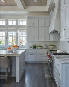 The kitchen features light gray stacked cabinets adorned with long satin nickel pulls paired with quartzite countertops and a light gray glazed tiled backsplash. The rustic wood floors are custom dark stained.
