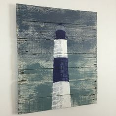 What guides your way? For years, light houses like this one lit up darkened journeys. Now they are an iconic image that reminds us that we all need our own guiding lite for those dark and stormy times.  This lighthouse is Blue and White on a gray background. The size is roughly 20 wide x 24 tall x 1 Please message me if you would like this piece in another color or size.  This wall art is made from reclaimed pallet wood. The years of weather and miles of wear creates a rustic look that…